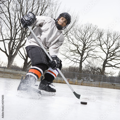 Photo  Boy in ice hockey uniform skating on ice rink moving puck.