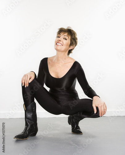 Fotografering Woman in spandex bodysuit and black cowboy boots smiling.