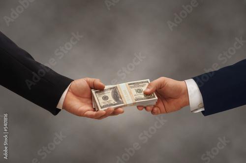 Fototapeta Two hands of businessmen passing a stack of dollars obraz