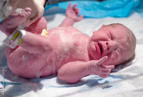Newborn getting his first bath after birth