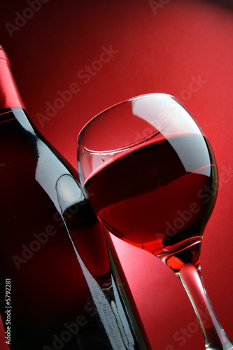 Papiers peints Vin Still-life with bottle and glass of wine over red background