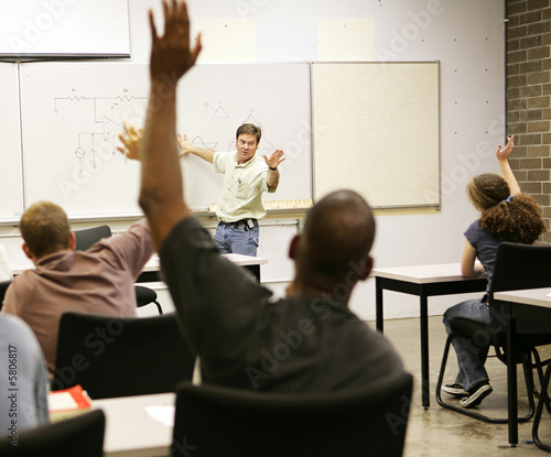 Canvas Print Adult education class raising hands to ask questions.