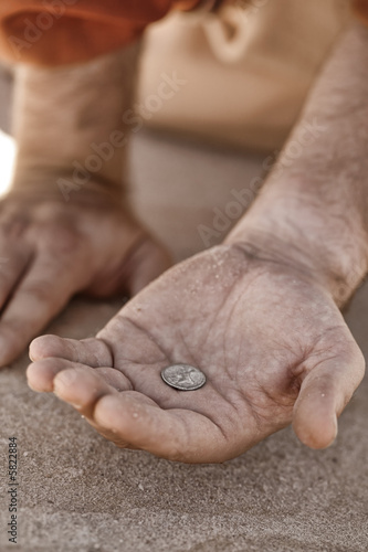 Fotografija  Hand holding a single coin - beggar, poverty, charity,