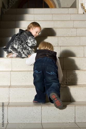 Photo sur Aluminium Akt Portrait of two cute children moving up stairs