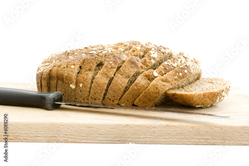 Photo  Slice brown soad bread on wooden board with knife