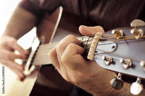 Fotografia, Obraz  Hands of a person playing an acoustic guitar close up