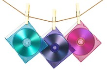 Three CDs In Colorful Cases Fixed With Pins On The Line