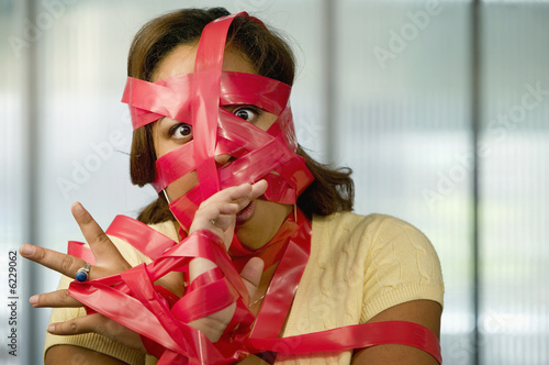 Fotografie, Obraz  Businesswoman wrapped in red tape