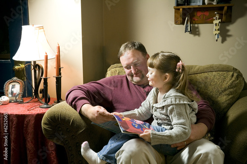 Photo  a little girl on grandpa's lap being read to.