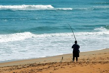 Surf Fisherman Catching Fish In Florida