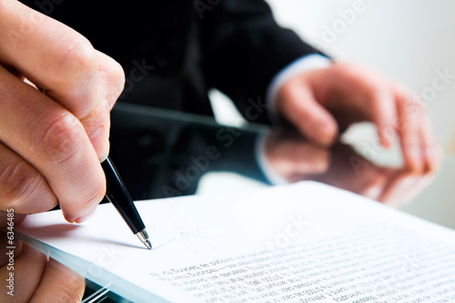 Fotografía  Closeup of business lady's hand with pen signing a contract