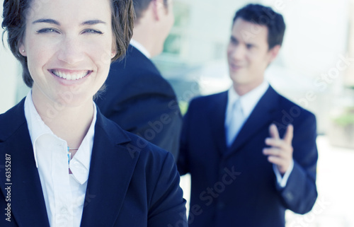 6e1a701afb5f business woman staring at camera while two businessmen talk - Buy ...