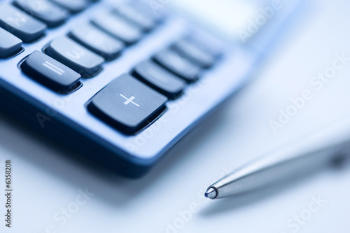 Calculator and pen in blue color, shallow focus Wallpaper Mural