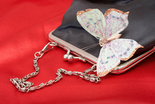 Black Purse With Colorful Butterfly Shot On Red Silk Background