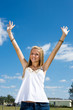 Beautiful blond teen girl outdoors raising her arms in freedom