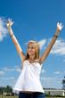 Blond teen girl outdoors raising her arms in praise.