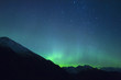 Leinwanddruck Bild - Northern lights making the sky green over the tops of mountains