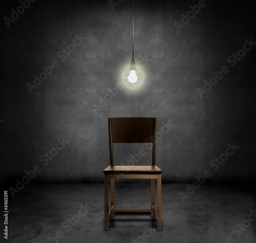 Fotografie, Obraz  An empty chair and hannging light bulb in a dark room