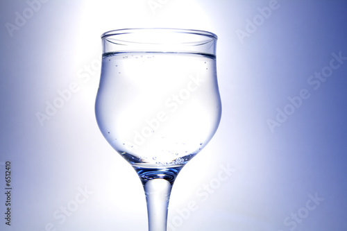 Nice goblet with drink and blebs on white-blue background Canvas Print