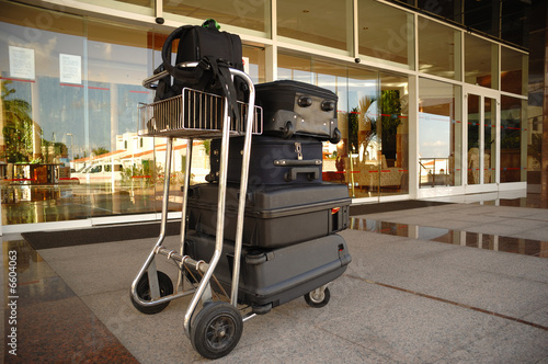 Fotografering  Trolley with suitcases in front of hotel