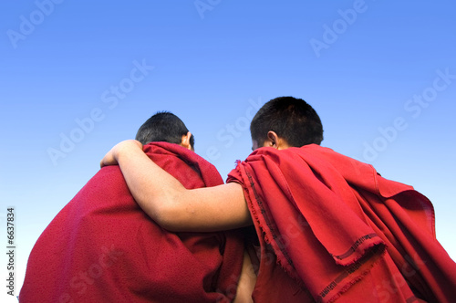 rear view of a monk holding another monk shoulder Canvas Print
