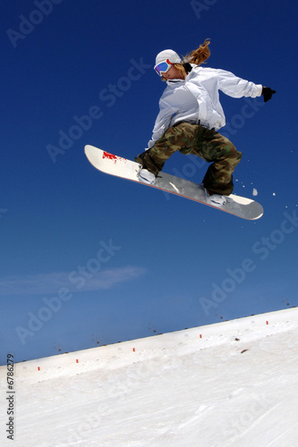 Fotografie, Obraz  woman snowboarder in flight with sky behind