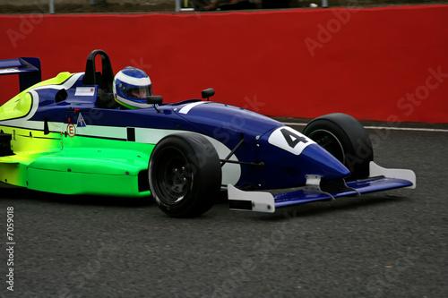 race car driving through race track pit lane