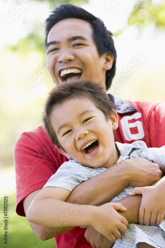 Fotografia  Asian father and son having fun in park