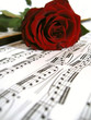 Red rose over sheet music