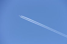 Plane In Blue Sky With Trail