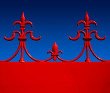 Red Wrought Iron Fleur De Lys Against Blue Sky