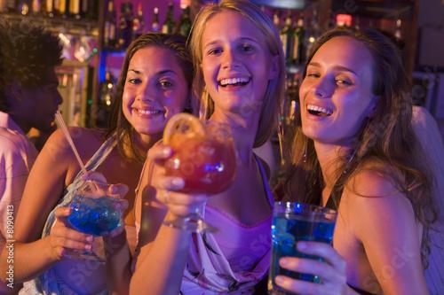 Fotografie, Obraz  Three young women with drinks in a nightclub