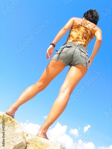 Young cute girl in the blue sky Canvas Print
