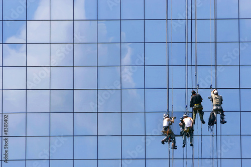 Photo window washers on glass building facade