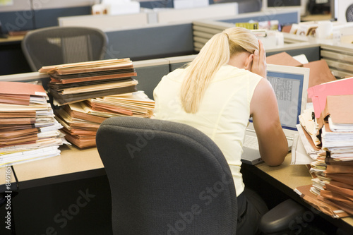 Canvastavla Businesswoman in cubicle with laptop and stacks of files
