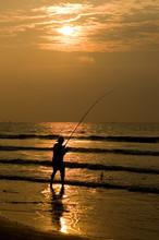 Fisherman Silhouettted In A Beach Sunrise