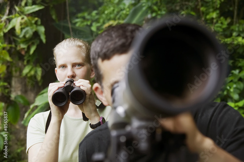 Pretty Woman with Binoculars and Man with Telescope in Jungle Billede på lærred