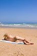 a beautiful woman suntanning on the beach