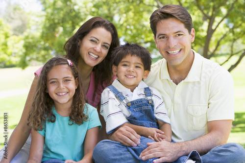 Valokuva  Family sitting outdoors smiling