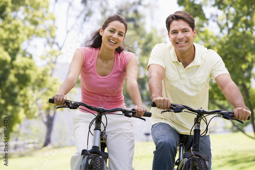 Photo Stands Cycling Couple on bikes outdoors smiling