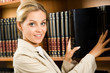 Portrait of business lady touching books that stand on shelf