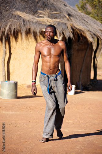 Foto  Crippled African man walking barefoot in the hot sand