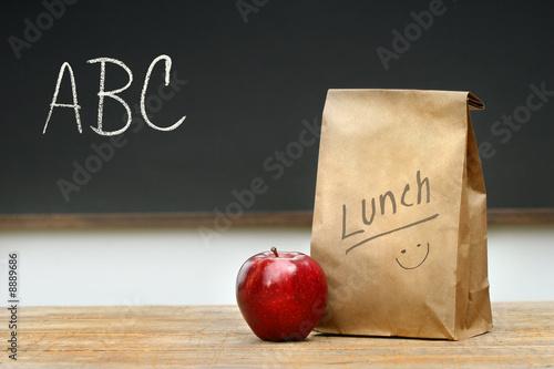 Fotografía Paper lunch bag on desk with apple