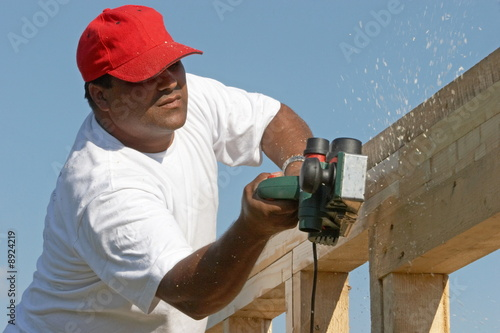 Photo Worker man polishing wood frame on anew construction