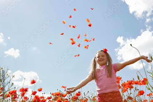 Photo Little girl meadow throwing poppy petals, blue sky in background