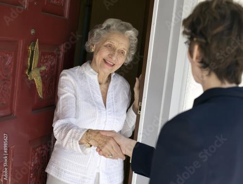 Fotografie, Obraz  Usmívající se starší žena pozdrav návštěvu u vchodových dveří