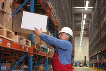 Senior Worker In Uniform Putting Box On Shelf In Warehouse
