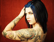 Pretty young woman with many tattoos on her back and arms