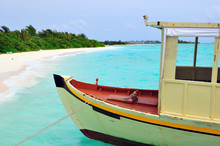 Old Traditional Boat Anchored On A Sandy Beach In Maldives