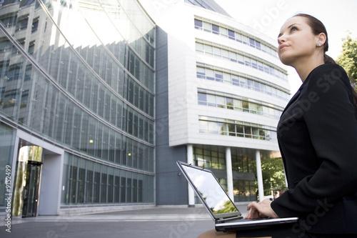 Foto  Businesswoman using laptop outside office